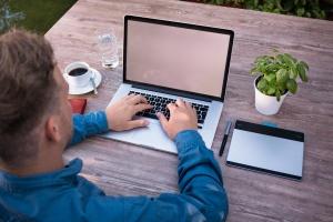 Čovek piše prodajni tekst na laptopu